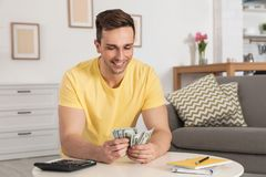 Happy man counting money at table. In living room stock photo