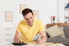 Happy man counting money at table. In living room royalty free stock photo