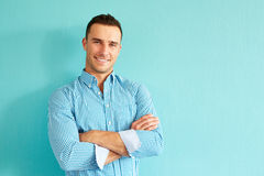 Happy man with crossed arms. Happy handsome man with crossed arms leaning against a turquoise wall Stock Image