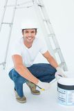 Happy man crouching while opening paint pot. Full length portrait of happy man crouching while opening paint pot over white background Stock Images