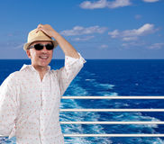 Happy man on a cruise. Holding his hat royalty free stock image