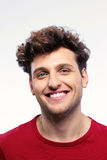 Happy man with curly hair. Portrait of a happy man with curly hair over grey background Royalty Free Stock Photos