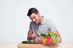 Happy man cutting cucumber Stock Image