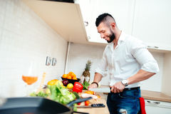 Happy man cutting vegetables for salad or soup. Young professional well dressed cook preparing food in new kitchen Stock Photos