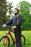 Happy man cyclist with bike among the green nature Stock Photo