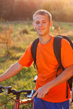 Happy man cyclist illuminated by sunlight Stock Photography