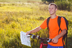 Happy man cyclist with map in hand. Illuminated by soft sunlight against a background of green nature Royalty Free Stock Photo