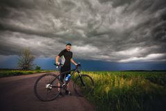 Happy man cyclist rides field road on a mountain bike. before the storm Stock Images