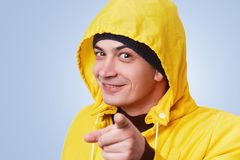 Happy man with dark appealing eyes wears yellow coat with anorak, points with fore finger diractly into camera, chooses someone, i. Solated over blue background royalty free stock images