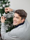 Happy Man Decorating Christmas Tree Stock Image