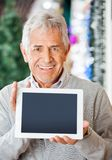Happy Man Displaying Digital Tablet In Christmas. Portrait of happy senior man displaying digital tablet at Christmas store stock photo
