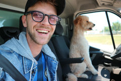 Happy man with dog in car Royalty Free Stock Image