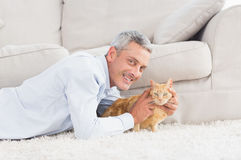 Happy man with dog lying on rug Royalty Free Stock Photography