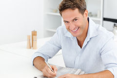 Happy man doing a crossword sitting at a table Royalty Free Stock Photo