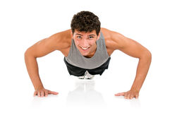 Happy man doing push ups. Young smiling fitness man doing push ups on floor, studio shot isolated on white background royalty free stock images