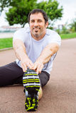 Happy man doing stretching exercises outdoors. Attractive and happy spotrsman doing stretching exercises outdoors in a track Stock Photo