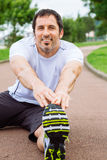Happy man doing stretching exercises outdoors. Attractive and happy spotrsman doing stretching exercises outdoors in a track Royalty Free Stock Photos