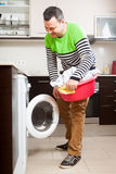 Happy man at domestic kitchen. Confident adult man standing in kitchen royalty free stock image