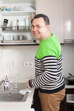 Happy man at domestic kitchen. Confident adult man standing in kitchen stock image