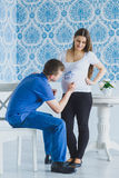 Happy man draws on his belly pregnant wife Stock Photography