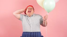 Happy man dressed in childish style laughing joyfully while holding air balloons, slow motion stock footage