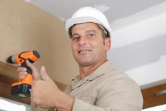 Happy man drilling wall with drill perforator royalty free stock image