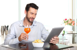 Happy man with drink and tablet at the bar Stock Photography