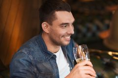 Happy man drinking beer at bar or pub. People, drinks, alcohol and leisure concept - happy young man drinking beer at bar or pub Stock Image