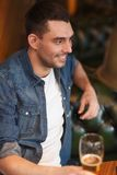 Happy man drinking beer at bar or pub Stock Photography