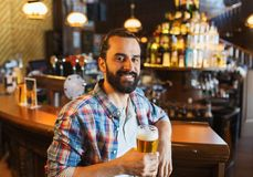 Happy man drinking beer at bar or pub. People, drinks, alcohol and leisure concept - happy young man drinking beer at bar or pub Stock Photography