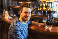 Happy man drinking beer at bar or pub Stock Photos