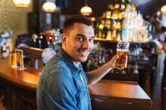 Happy man drinking beer at bar or pub Stock Photo