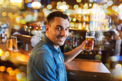 Happy man drinking beer at bar or pub. People, drinks, alcohol and leisure concept - happy young man drinking beer at bar or pub Stock Photos