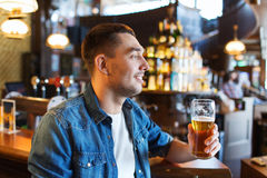 Happy man drinking beer at bar or pub Stock Image