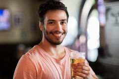 Happy man drinking beer at bar or pub. People, drinks, alcohol and leisure concept - happy young man drinking beer at bar or pub Stock Photo