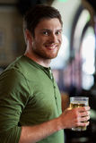 Happy man drinking beer at bar or pub. People, drinks, alcohol and leisure concept - happy young man drinking beer at bar or pub Royalty Free Stock Images