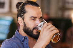 Happy man drinking beer at bar or pub. People, drinks, alcohol and leisure concept - happy young man drinking beer from glass at bar or pub Stock Photos