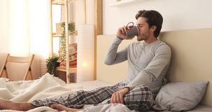 Happy man drinking coffee in bed. Relaxed young man drinking morning coffee in bed stock video