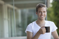 Happy man drinking coffee. Happy man with a cup of coffee relaxing outdoors Stock Image