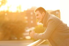 Happy man drinking coffee looking away from a balcony. Side view portrait of a happy man drinking coffee looking away from a balcony in winter at sunset stock photography