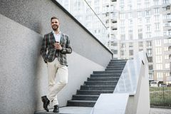 Happy man drinking coffee on staircase. Full length portrait of joyful businessman enjoying hot beverage while relaxing outdoor. He is standing on steps and Stock Image
