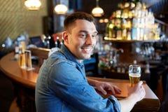 Happy man drinking draft beer at bar or pub Stock Photography