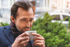 Happy man drinking hot beverage outdoors. Dreamful businessman is enjoying coffee on street. He is smelling cup with pleasure and smiling Stock Photos