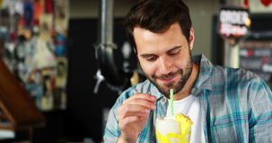 Happy man drinking milkshake