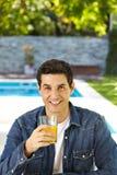 Happy man drinking orange juice royalty free stock photography