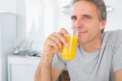 Happy man drinking orange juice in kitchen. Looking at camera Stock Photo