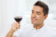 Happy man drinking red wine from glass at home. Profession, drinks, leisure, holidays and people concept - happy man drinking red wine from glass at home Stock Photos