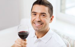 Happy man drinking red wine from glass at home. Profession, drinks, leisure, holidays and people concept - happy man drinking red wine from glass at home Royalty Free Stock Images