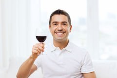 Happy man drinking red wine from glass at home. Profession, drinks, leisure, holidays and people concept - happy man drinking red wine from glass at home Stock Images