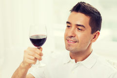 Happy man drinking red wine from glass at home. Profession, drinks, leisure, holidays and people concept - happy man drinking red wine from glass at home Royalty Free Stock Photos